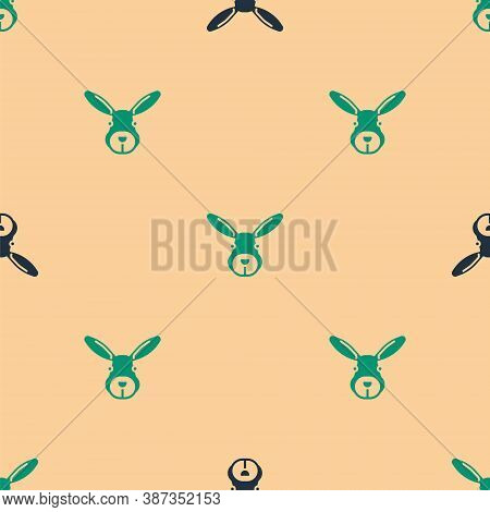 Green And Black Rabbit Head Icon Isolated Seamless Pattern On Beige Background. Vector