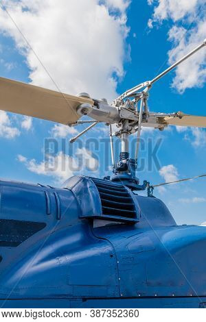 Cowling And Rotor Assembly On Helicopter With Blue Cloudy Sky In Background.