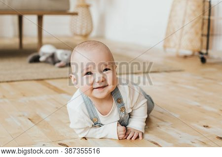 Baby Is Lying On The Floor. Smiling Six Month Old Baby In A Beautiful Interior.sly Kid