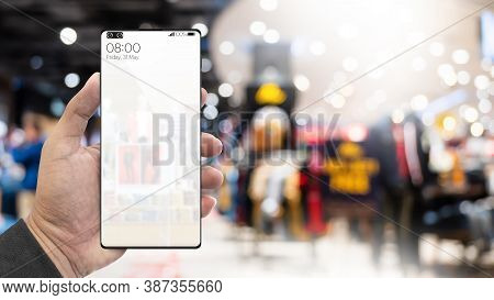 Hand Holding Smartphone With Blur Interior In The Mall. Black Friday Shopping App On A Mobile Phone