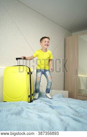 Cheerful Boy Has Come On Vacation And Is Happy To Jump On The Bed In A Hotel Room.