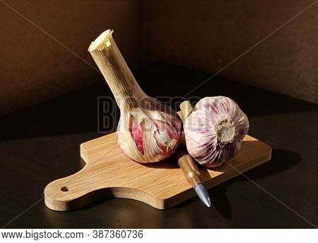 Two Garlic Bulbs And Rifle Cartridge With Silver Bullet On Wooden Cutting Board Against A Low Key Ba