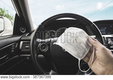 Medical Face Mask Holding On Driver Hand Inside To The Car , Coronavirus (covid-19) Prevention Conce