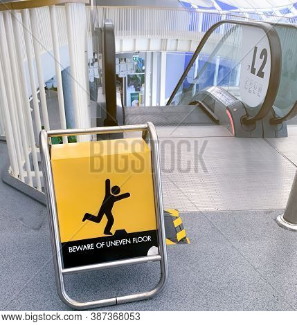 Beware Uneven Floor Warning Sign On Yellow Board In Front Of Escalator In Shopping Mall. Beware Unev