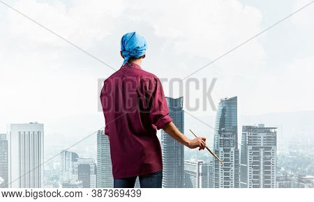 Young Male Painter Artist Holding Paintbrush. Back View Of Painter In Shirt And Bandana On Backgroun