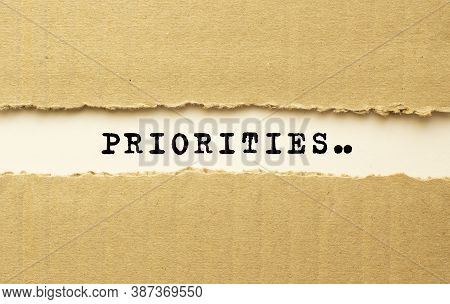 Text Priorities Appearing Behind Torn Brown Paper. Top View.