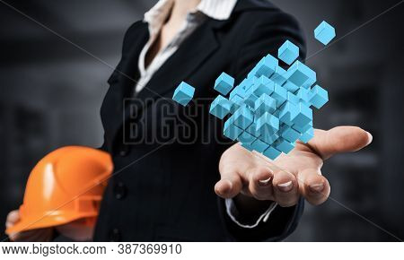 Businesswoman Holds In Palm Abstract 3d Cube Model. Woman Engineer In Business Suit With Orange Safe