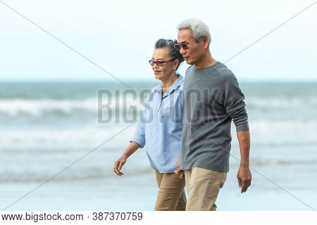 Lifestyle Asian Senior Couple Happy Walking And Relax On The Beach.  Tourism Elderly Family Travel L