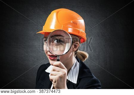 Building Inspector Looking Through Magnifying Glass. Young Construction Specialist In Safety Helmet