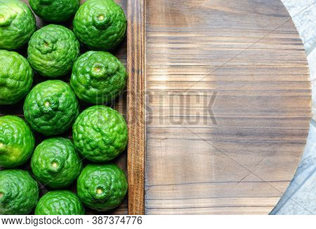 Many Of The Kaffir Lime Fruits Are Green And Fresh, Placed On Softwood Material With Beautiful Patte