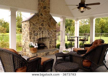 Beautiful outdoor living space with fireplace and vaulted ceiling. poster