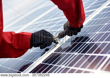 Installing Solar Panels. Close-up Of Mans Hands In Orange Uniform And Black Gloves With Wrench In Hi