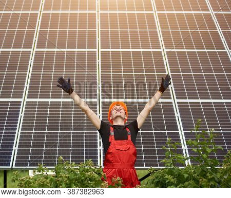 Happy Successful Worker Near Solar Station Raising His Hands On A Background Of Photovoltaic Panels