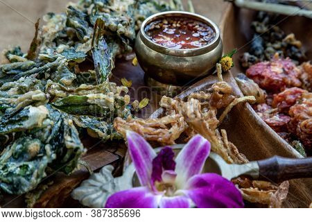Close-up Of Crispy Flowers, Crispy Herbs And Crispy Vegetables Served  With Sweet Sauce In A Wooden