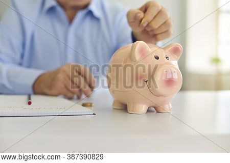 Senior Man Saving Money And Putting Coin In Cute Shiny Piggy Bank Standing On Desk