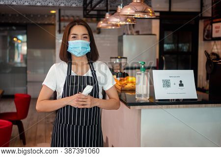 Asian Waitress Woman Wearing Face Masks And Holding An Infrared Forehead Thermometer To Check Body T