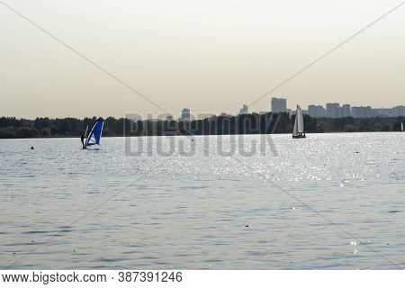 Windsurfer. Man Is Surfing On The Background Of Skyscrapers. Man On A Windsurf Board. Windsurfing In