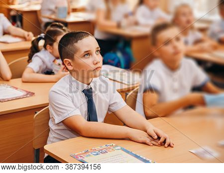 Portrait Of Beautiful School Boy In Elementary School Classroom. Happy Schoolboy Sitting With Face M