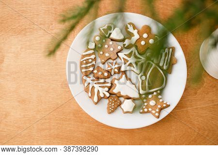 Christmas Gingerbread Cookies On White Plate On Wooden Background With Fir Branches