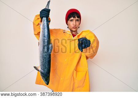 Beautiful brunettte fisher woman wearing raincoat holding fresh salmon pointing with finger to the camera and to you, confident gesture looking serious