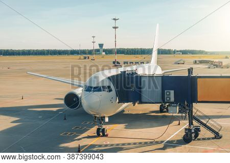 The Aircraft In The Parking Lot Is Attached To The Boarding Bridge For Boarding Passengers From The