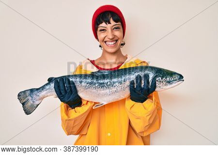 Beautiful brunettte fisher woman wearing raincoat holding fresh salmon smiling with a happy and cool smile on face. showing teeth.