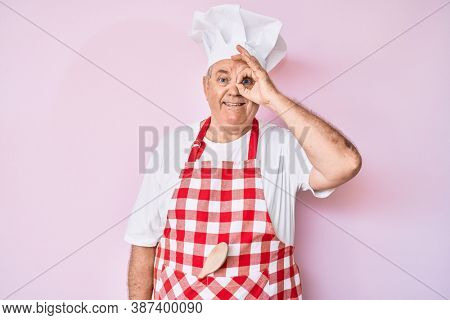 Senior grey-haired man wearing professional baker apron doing ok gesture with hand smiling, eye looking through fingers with happy face.