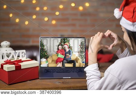 Young Smiling Woman Wearing Red Santa Claus Hat Making Video Call On Social Network With Family And