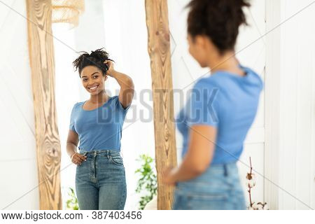 Female Beauty And Self-confidence. Cheerful African Lady Posing Near Mirror After Slimming And Succe