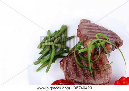 business lunch grilled meat beef steaks strips on white plate with sweet pea and tomatoes isolated over white background