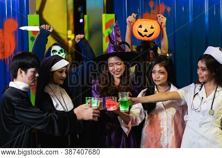 Group Of Asian Friends Rest In A Nightclub With Colored Cocktails Wearing Halloween Costumes At Part