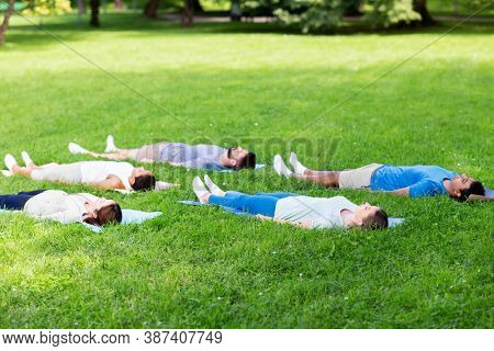 fitness, sport and healthy lifestyle concept - group of happy people doing yoga corpse pose or savasana at summer park