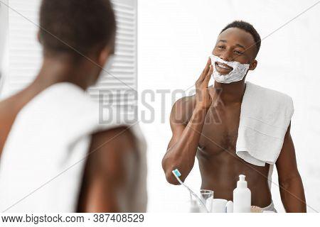 Shirtless Black Man Preparing For Shaving Foaming Face Applying Shave Foam Standing Near Mirror In M