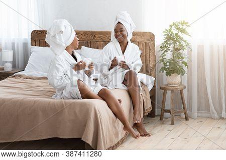 Beautiful Black Ladies Sitting On Bed, Wearing Bathrobes, Drinking Coffee And Having Conversation, C