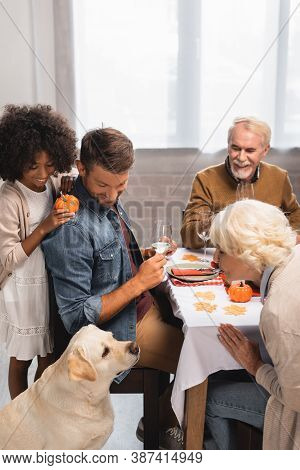 Focus Of Multiethnic Family Looking At Golden Retriever During Thanksgiving Dinner