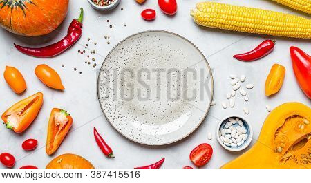 Frame Of Yellow And Orange Vegetables On A Gray Background