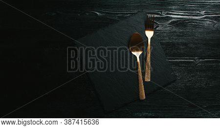 Kitchen Background. Menu Design. Black Slate Plate On A Black Wooden Background.