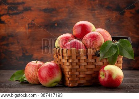 Ripe garden apple fruits in basket on wooden table with copy space