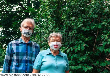 Elderly Couple Stands Against A Background Of Green Foliage In Disposable Masks With Mustaches And L