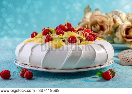 Traditional Pavlova Dessert With Mascarpone Cream Served With Fresh Raspberries, Lemon Cream And Lim