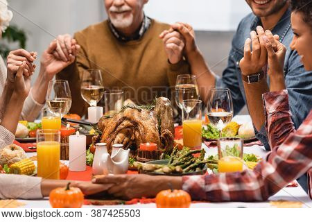 Cropped Of Pleased Multiethnic Family Holding Hands On Thanksgiving