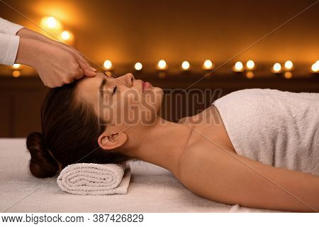 Relaxed Young Woman Getting Healing Head Massage At Modern Luxury Spa In Romantic Atmosphere, Side V