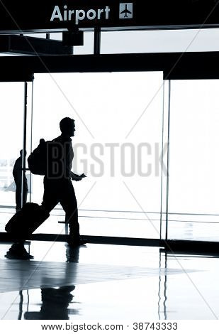 Business travel photo concept - Silhouette of business man walking in airport with luggage