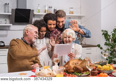 Focus Of Multicultural Family Waving At Digital Tablet During Video Call And Thanksgiving Celebratio