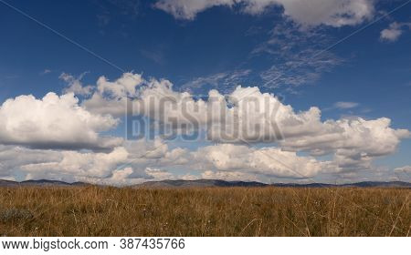 Big White Clouds Above The Steppe Meadow In Khakassia. Landscape With A Grass, Hills And The Sky.