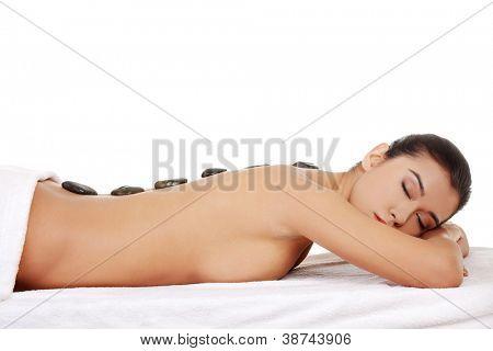 Beauty woman relaxing in spa. Stone massage.