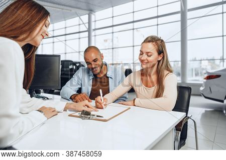 Beautiful Young Couple Signs Documents At Car Dealership Showroom