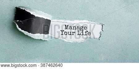 The Text Manage Your Life Appearing Behind Torn Brown Paper