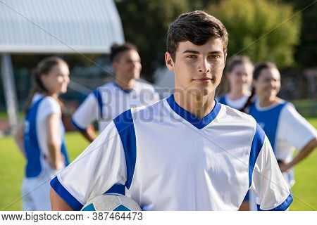 Portrait of young satisfied soccer player holding a football and looking at camera. Young man during training on soccer field. Proud teen guy training on soccer field with school teammates.