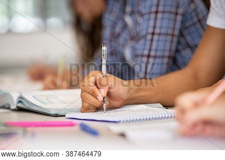 Close up of african student hand on table in classroom taking notes. Closeup of guy hand studying for exam in high school library. University student taking notes in classroom during lecture.